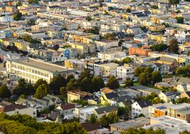 The golden glow of the setting sun hits the facade of thousands of homes in San Francisco, California